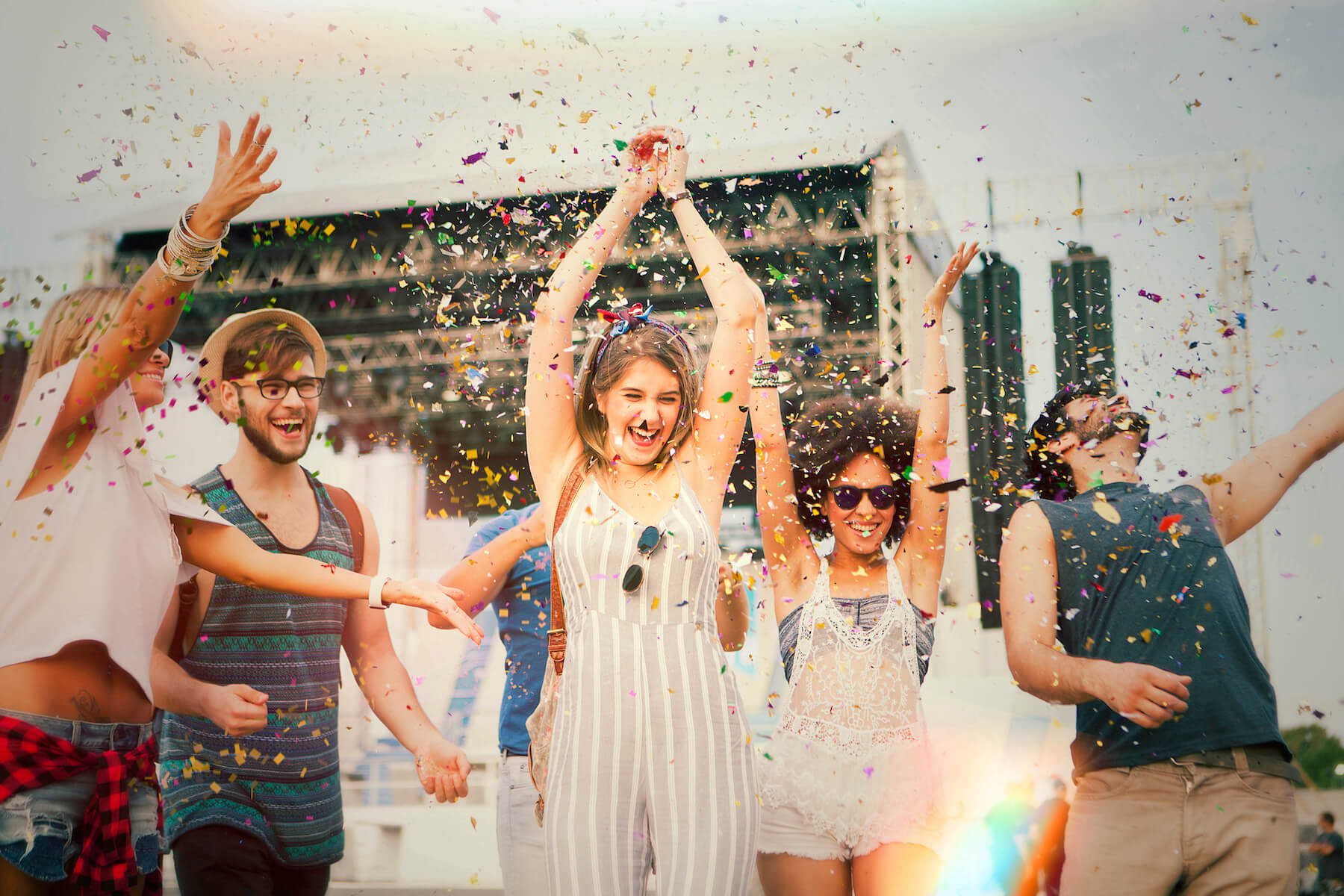 Group of friends celebrating festival event together with confetti